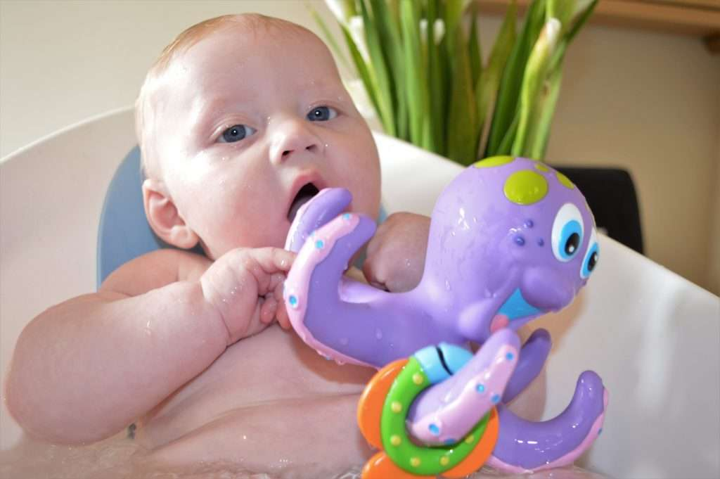 William in his baby bath with purple octopus toy.
