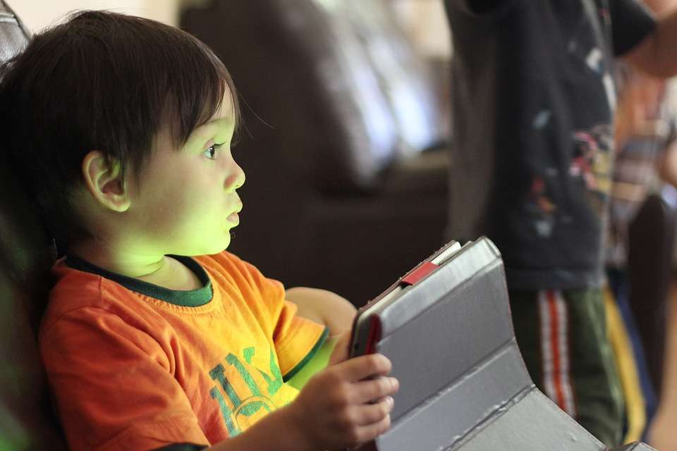 A child stares into the distance with the blue light of a tablet screen in front of him