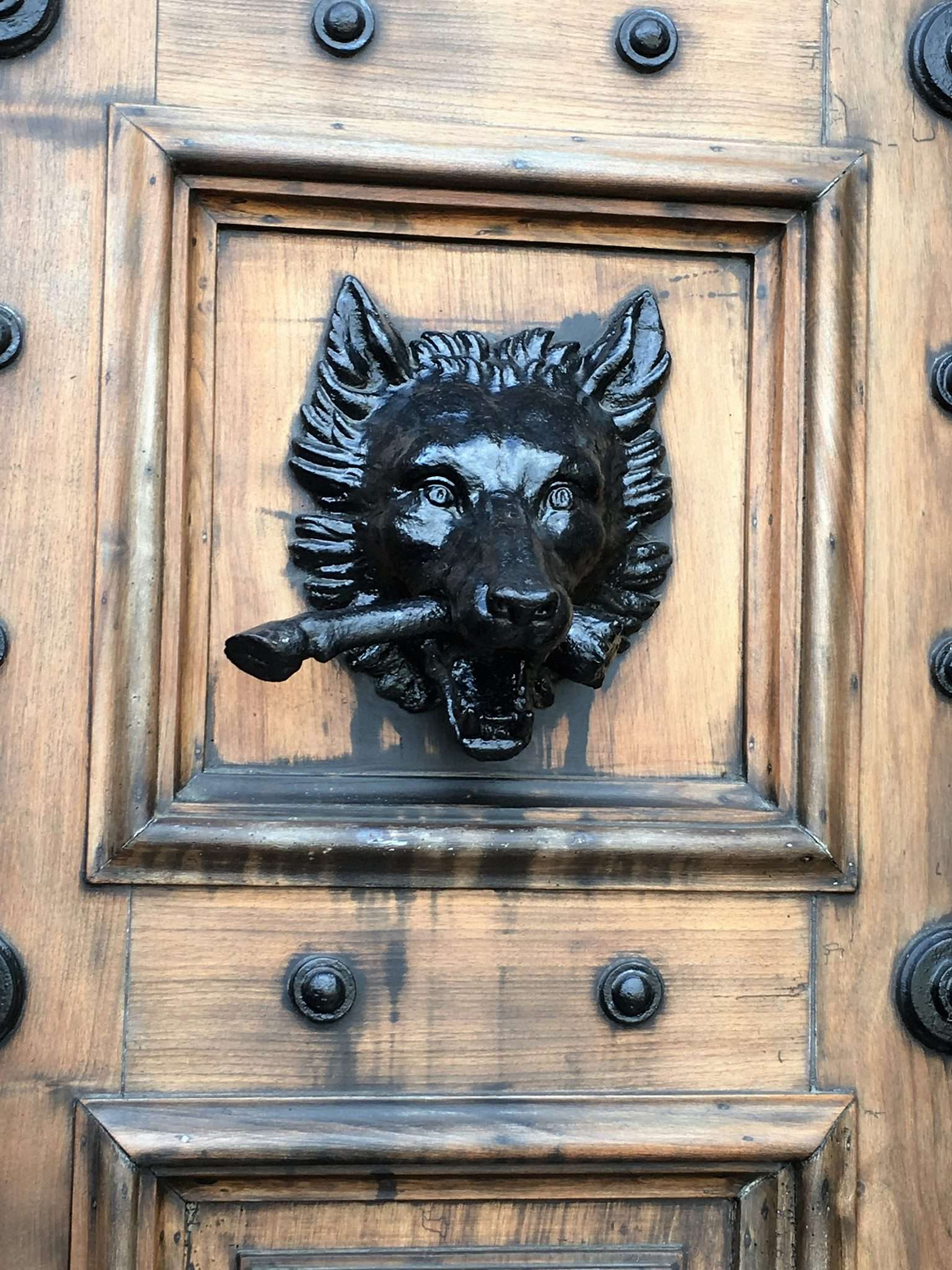 A large wooden entry door with a cast iron door knocker in the shape of a wolf with a stick in the mouth