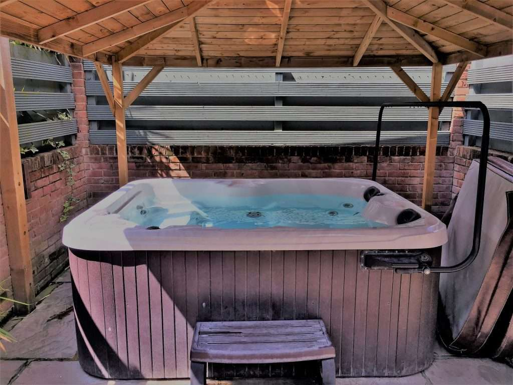 Large covered hot tub in a private patio garden
