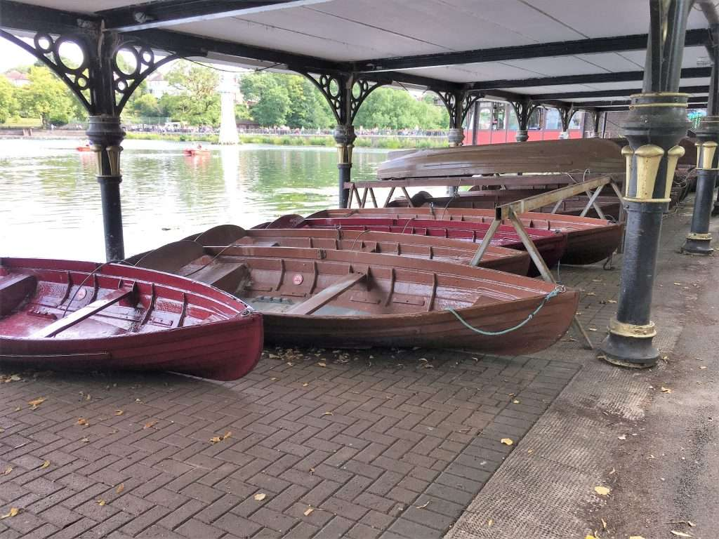 Five wooden boats by the side of Roath Park Lake, with the lighthouse in the background