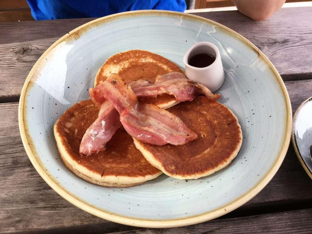 Three pancakes with bacon and a pot of maple syrup.