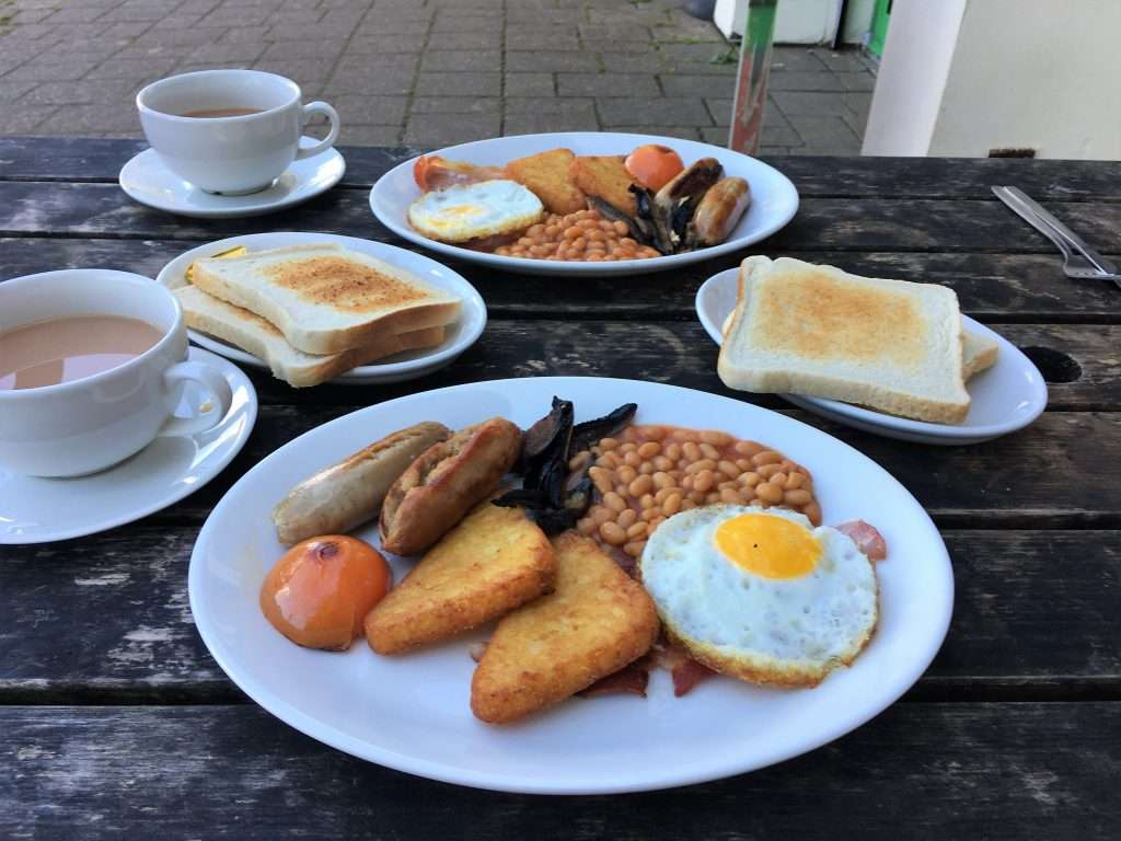 Two plates of cooked breakfast with sausages, fried egg, bacon, mushrooms, tomato, hash browns and baked beans, slices of toast and cups of tea. Set outside on a wooden table.