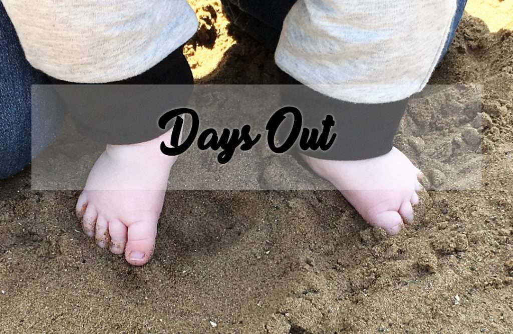 Baby feet standing in the sand of the beach