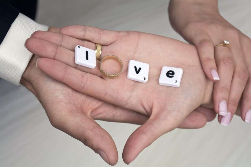 Two hands together, with three scrabble tiles L, V and E, with a wedding ring as the O - spelling love.