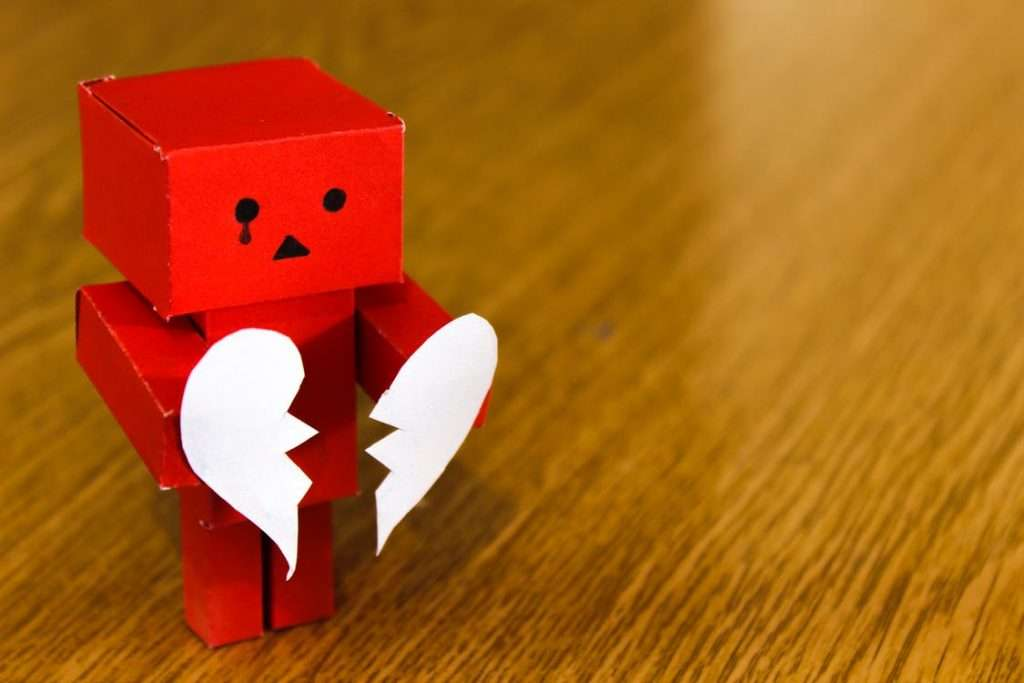 A sad red man holding a white heart to signify depression and anxiety