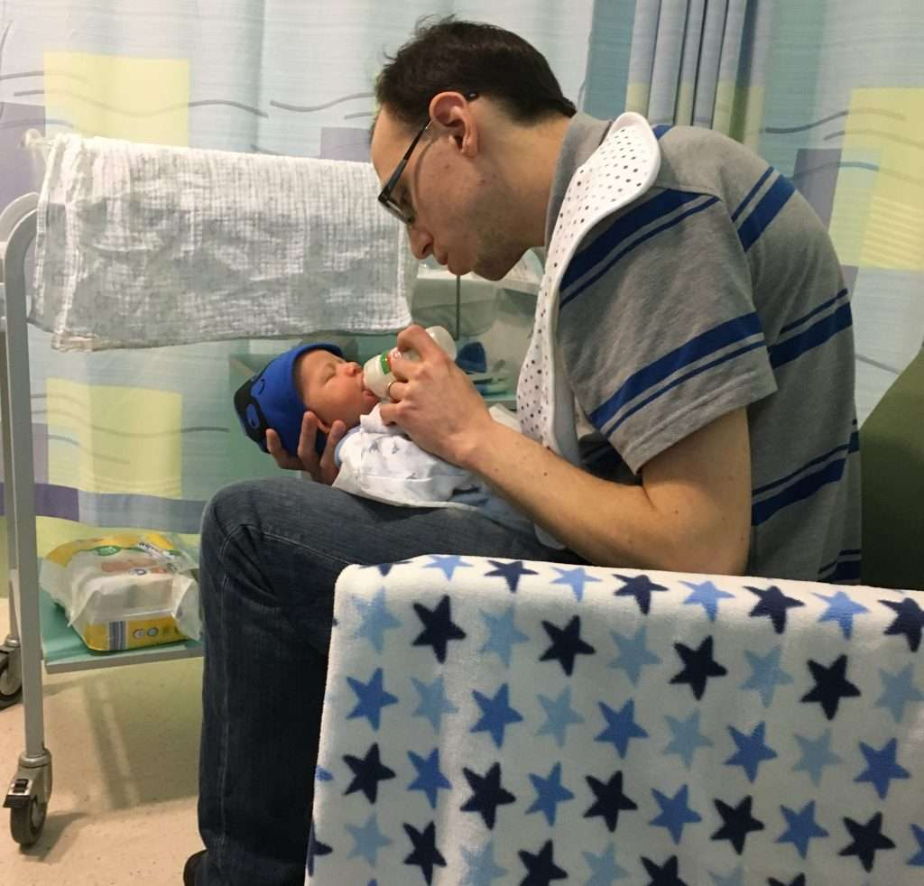 Christy's husband sitting in a hospital chair feeding a newborn