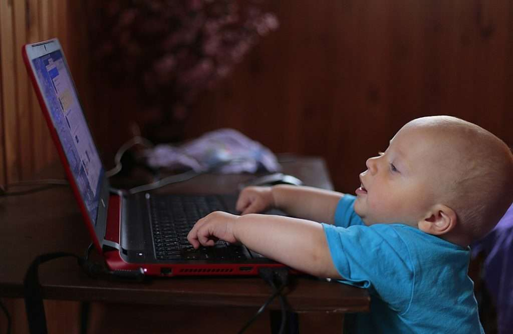 A young child reaching up to a laptop