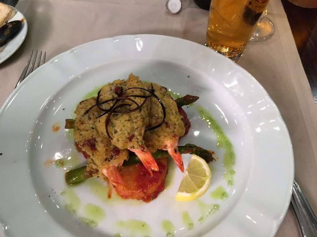 A plate of giant prawns covered in sauce
