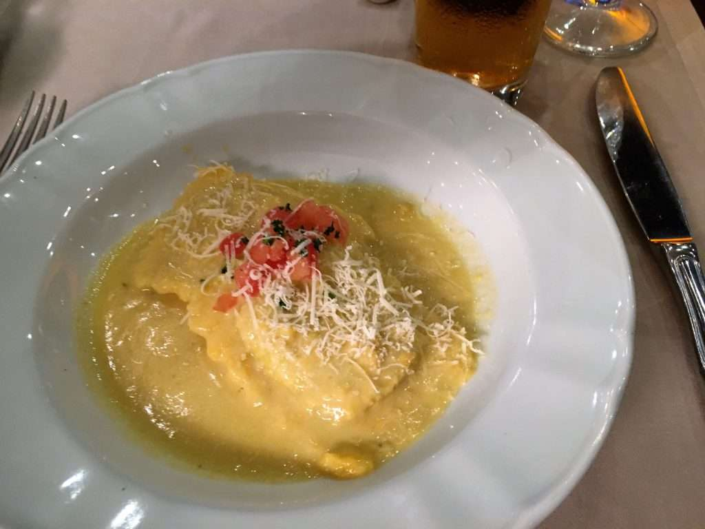 A plate of two giant ravioli in a cheese sauce