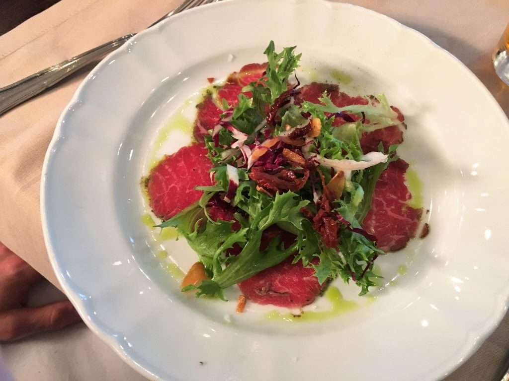 A plate of beef carpaccio and salad