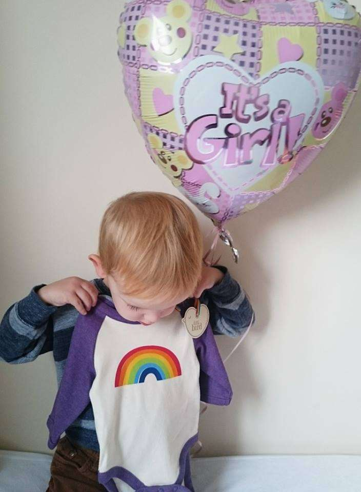 Gender reveal of a young boy holding up a purple rainbow onesie and a pink balloon that says It's a Girl