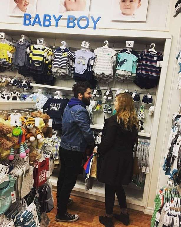 Gender reveal by standing in front of the baby boy clothes in a shop