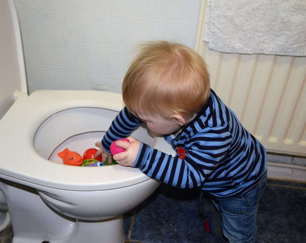 10 month old boy standing over a toilet filled with toys
