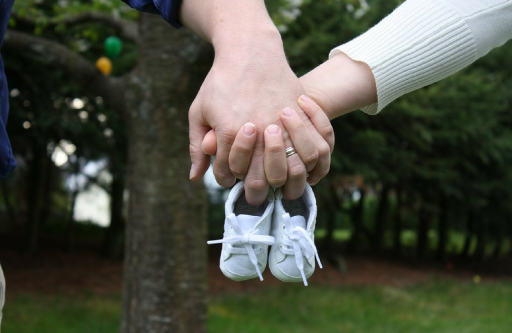 Two hands holding a tiny pair of blue shoes