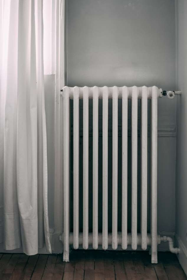 A large radiator next to a window with a curtain.