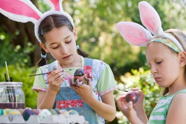 Two girls painting easter eggs at an easter event, wearing bunny hats.