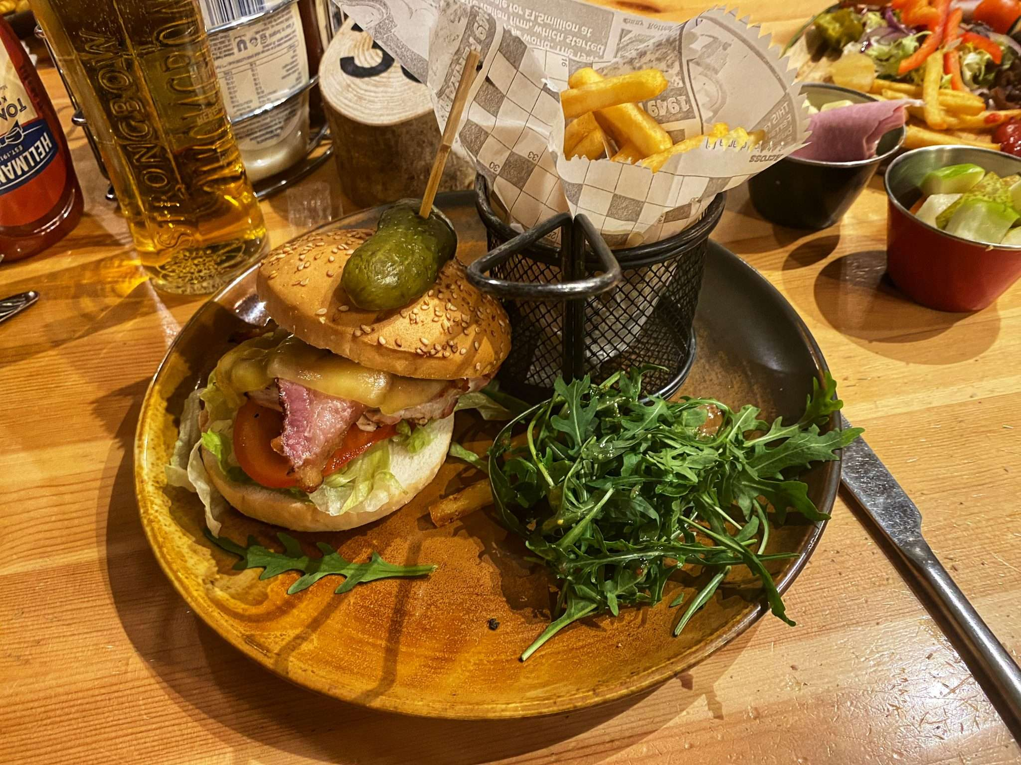 A chicken breast with bacon and cheese in a gluten free bun with a basket of fries and salad.