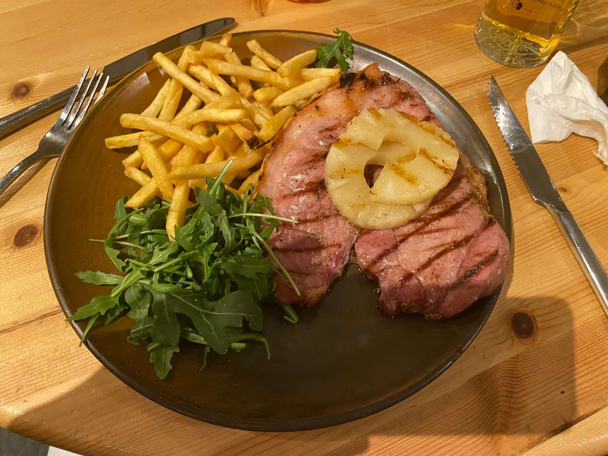 A 13oz gammon steak and large pile of fries and salad, with two rings of pineapple