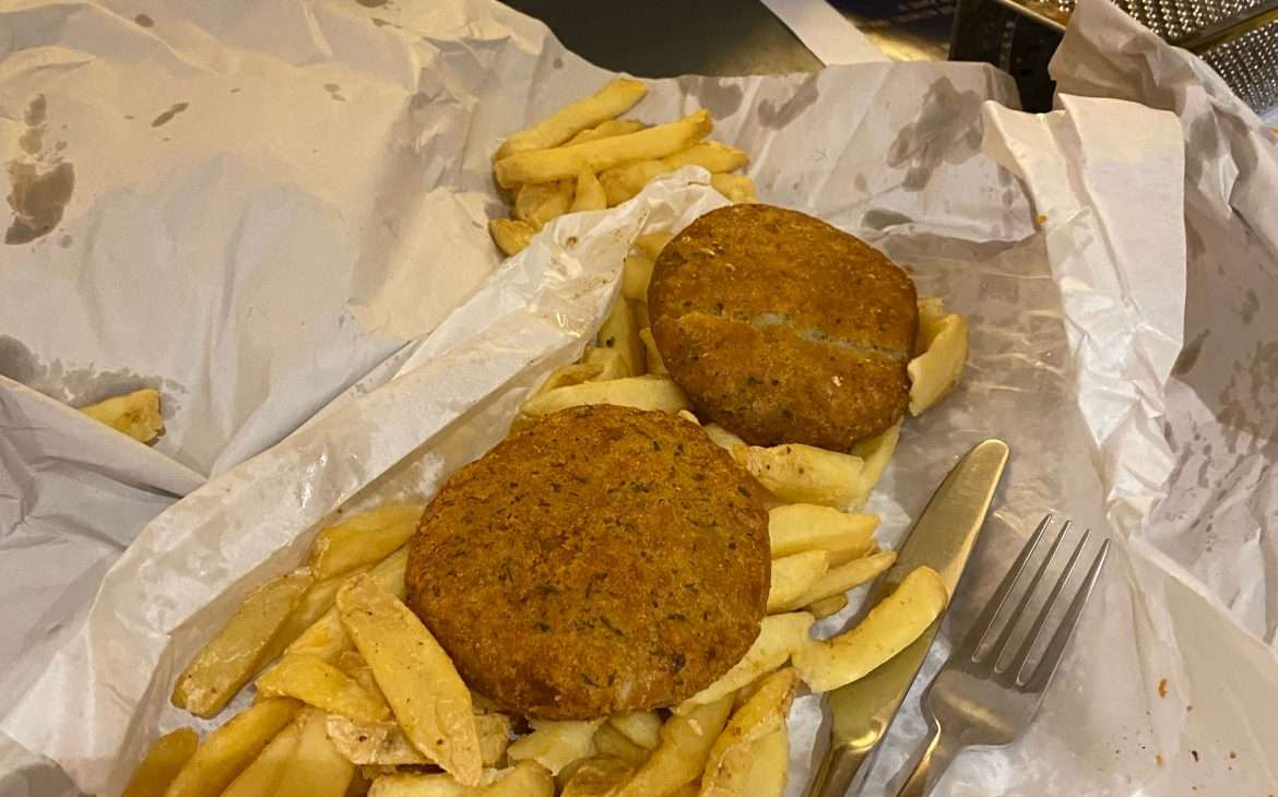 Two gluten free fishcakes and a large pile of chip shop chips on a paper bag